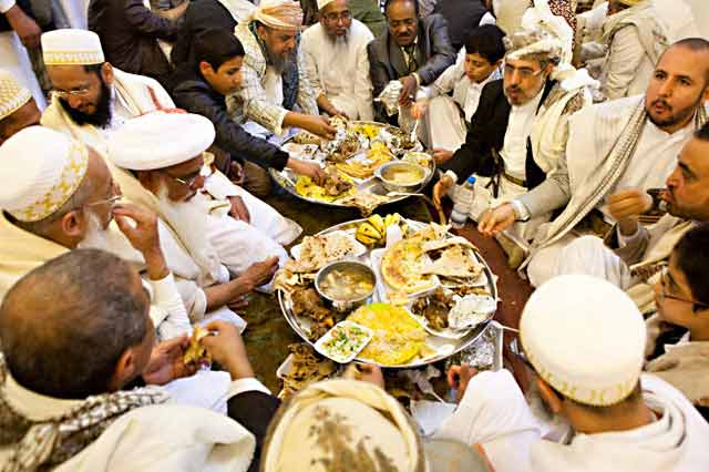 Photo of many Indian and Yemeni men sitting around platters of food by Maarten de Wolf.