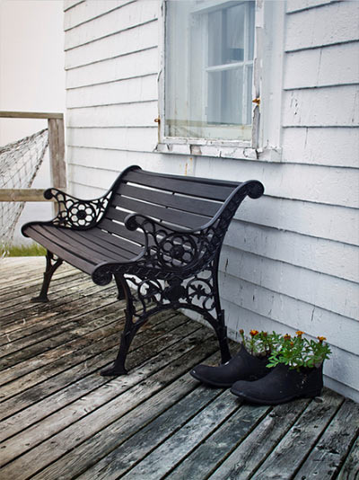 Close up image of a bench, fish net and rubber boot planters on a porch in Nova Scotia, Canada by Jim Autin.