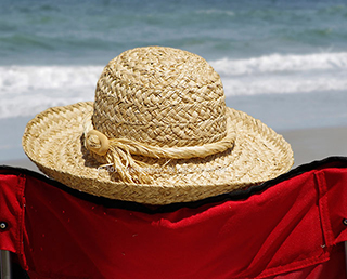 Protect your face from UV rays: Image of straw hat, chair and surf at Jacksonville Beach, Florida by Marla Meier.