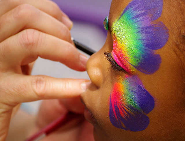 Image of a little girl getting a butterfly painted on her face in bright colors by Marla Meier. Photography Model Release
