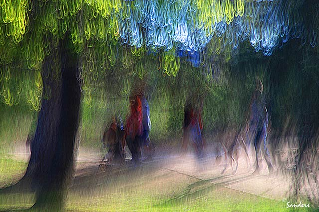 Photo Impressionism technique: image of people on a path between trees where camera shake and sunlight streaming through the leaves resulted in bright loops of light by Gerald Sanders.