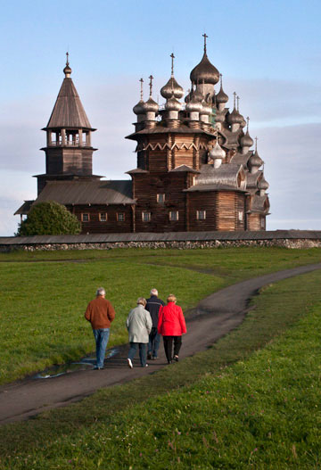Landscape photo of people walking to a church in Kizhi Island, Russia by Noella Ballenger