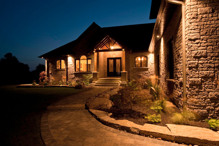 Exterior photo of home at dusk with house lights on by Randy Romano