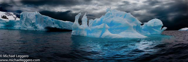 Dark stormy skies over a aqua colored iceberg in Antarctica by Michael Leggero.