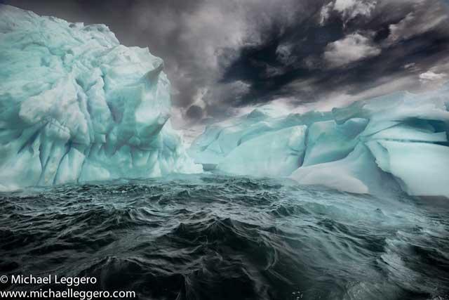 Dark stormy skies over rough seas an iceberg in Antarctica by Michael Leggero.