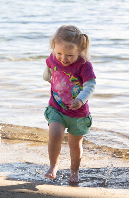 Photo portrait of a toddler on the beach running from the surf by Cathy Topping.