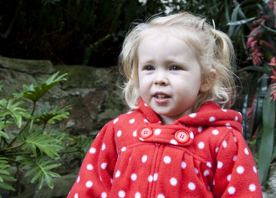 Close-up photo portrait of a toddler in a red and white polka dot top - outside in front of plants by Cathy Topping.