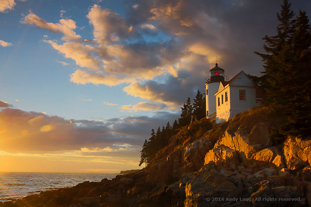 A white lighthouse in Maine is lit by the golden setting sun creating a harmonious scene by Andy Long.