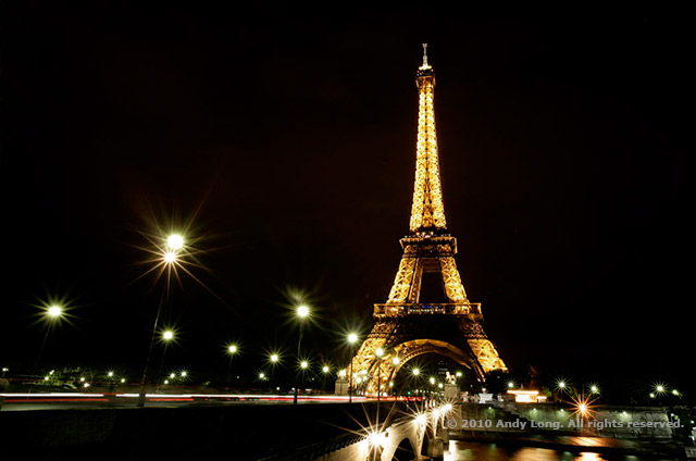 Image of the Eiffel Tower lit at night with leading lines of light posts and the lights from moving cars by Andy Long.