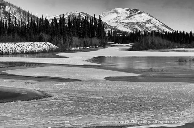 Black and white image showing curves in an icy pond that lead the eye to a mountain by Andy Long.