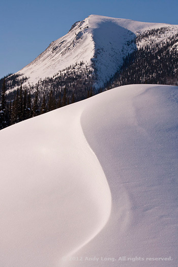 A snow covered hill with an S curve merge with the curve in the mountain top by Andy Long.
