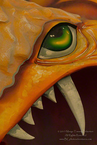 Close-up image of an orange dinosaur sculpture with big teeth and a green eye by Margo Taussig Pinkerton.