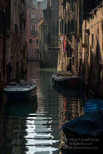 Image of boats floating on a Rios (narrow water chanenl) between building in Venice, Italy by Margo Taussig Pinkerton.