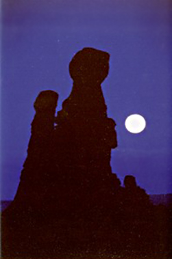 Full moon photography: silhouetted rock formations in front of full moon by Andy Long.