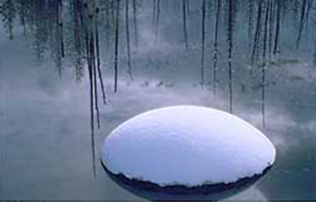 Image of a rock with snow on top in a winter pond in Wyoming by Brenda Tharp.