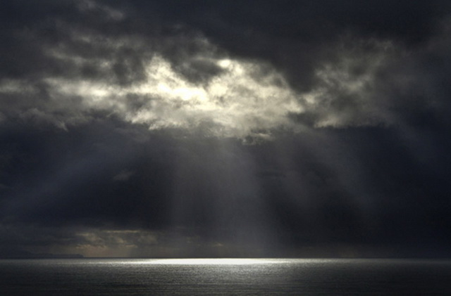 Photo of light beams through clouds to top of ocean by Noella Ballenger