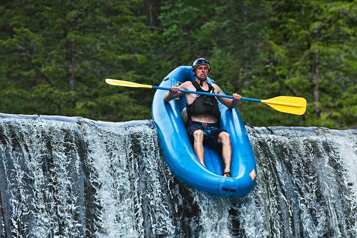 Stop action photography: Rafter going over waterfall by Brad Sharp.