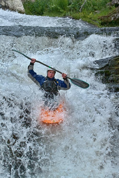 Stop action photography: Man kayaking in waterfall by Brad Sharp.