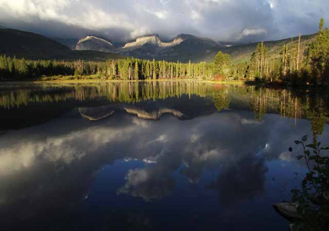 Photo adventures day hike: Continental Divide reflection in lake with dark, stormy clouds, Rocky Mountain National Park by Jeff Doran.