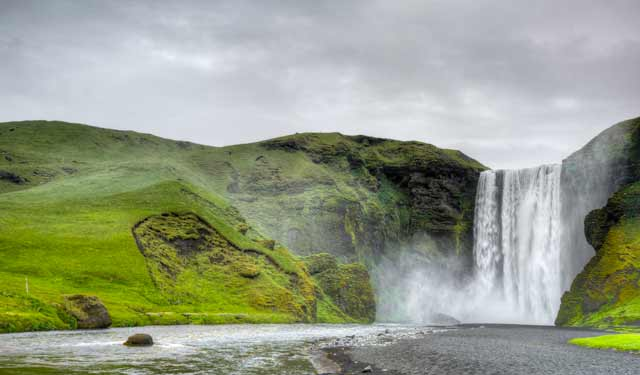 Photographic Travels in Iceland: Image of Skógafoss Falls and brilliant green landscape by Michael Legerro.