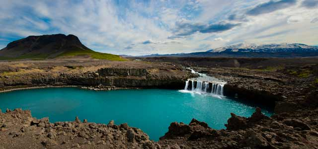 Photographic Travels in Iceland: Image depicting a diverse landscape of lava rock, aqua blue lake with mountain backdrop by Michael Legerro