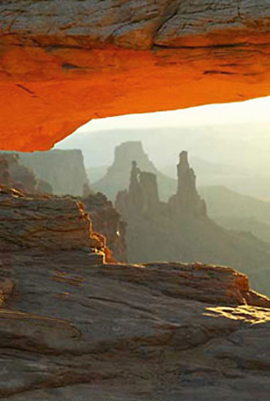 Image of Mesa Arch with rock formation showing through by Jim Altengarten.