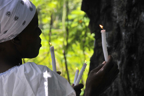 Photo of pilgrim lighting candle during the Saut d'Eau annual purification pilgrimage in Haiti