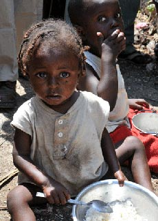 Photo of toddler eating bowl of rice in the camp of Thozin, outside of Port-au-Prince, Haiti