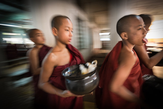 Motion blur shown while young monks start their lunch in Myanmar by Harry Fisch.
