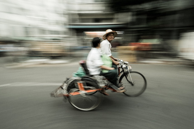 Motion blur used to show two men on a tricycle riding down a street in Myanmar by Harry Fisch.