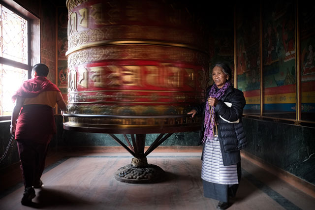 A woman in Bodnath, Nepal is praying next to a giant spinning prayer wheel by Harry Fisch.
