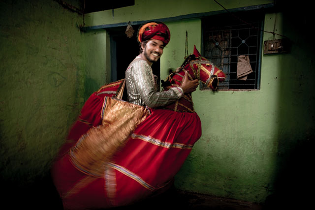 Motion is shown as a young man in a colorful horse costume acts before a festival in New Delhi, India by Harry Fisch.