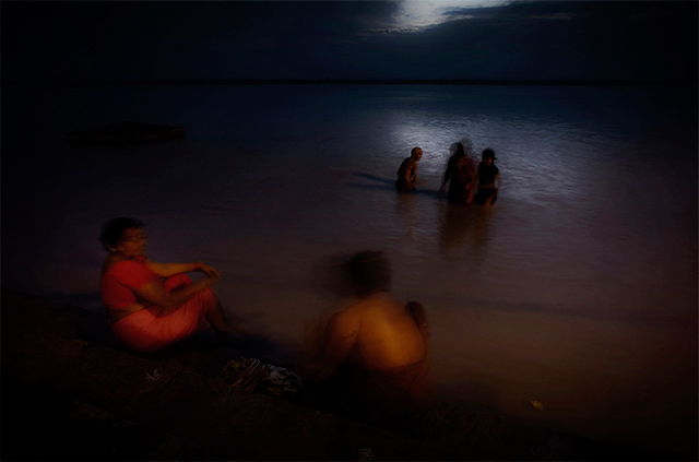 Motion blur is used to show women preparing the prayers next to the Ganges in Varanasi, India by Harry Fisch.