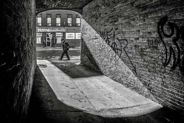 Black and white image created from inside a brick alley with a man walking past and harware store sign in the back by Randall Romano.