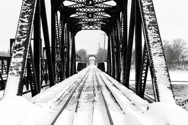 Black and white image looking down a train bridge in the snow by Randall Romano.