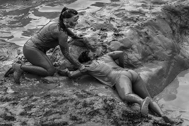 Black and white image of two women covered in mud outside of a mud hole by Randall Romano.