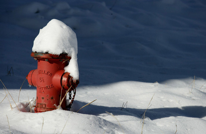 Red fire hydrant with snow piled on top by Andy Long.