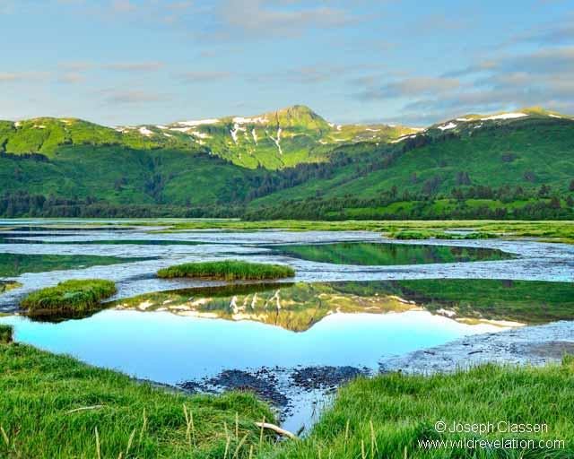 The lush greenery and mountains reflect in the waters of Anton Larson Lake on Kodiak Island by Joseph Classen.
