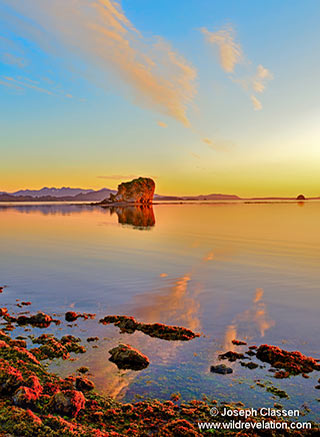 A summer orange sunrise and rock reflections near Brookers Lagoon on Kodiak Island, Alaska by Joseph Classen.
