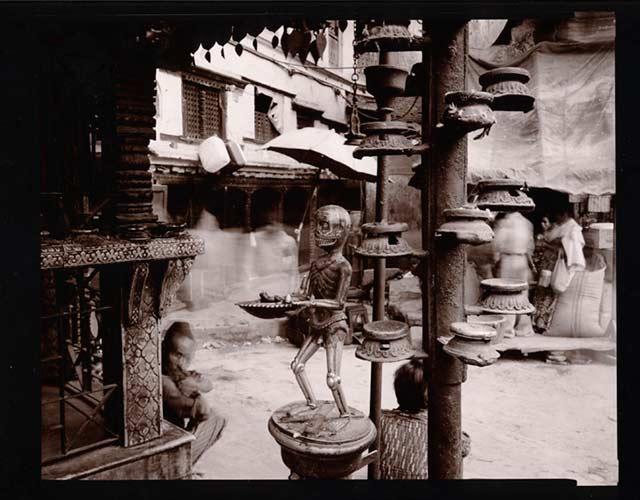 Black and white street scene of a Skeleton on Shrine, Kathmandu, Nepal by Linda Connor.
