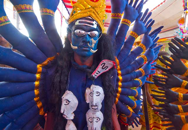 Dasara festival in India: person dressed as Goddess Kali - blue painted face, royal blue and gold costume with many arms and a skull necklace by Kris Hariharan.