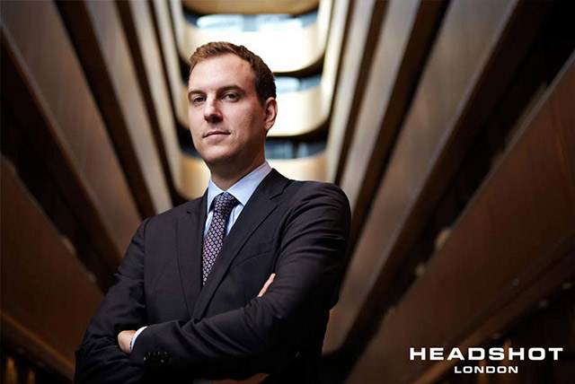 Corporate environmental portrait of a man standing within an office building by Headshot London Photography.