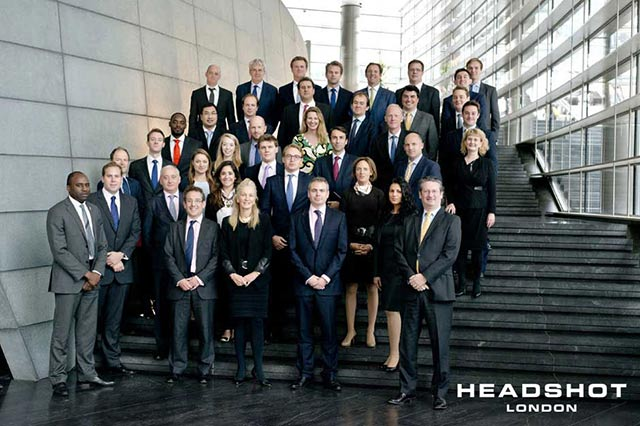 Corporate group portrait of men and women on building stairs by Headshot London Photography.