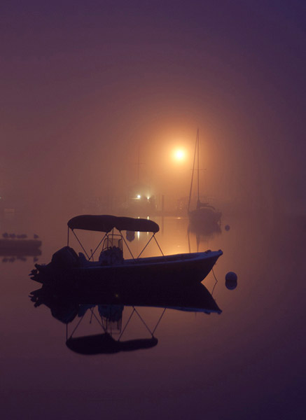 Fog and reflection photo of boat in a marina by Jeff Gallo