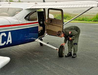 Aerial photography: Image of pilot doing a preflight check on a Cessna 182 by Allen Moore.