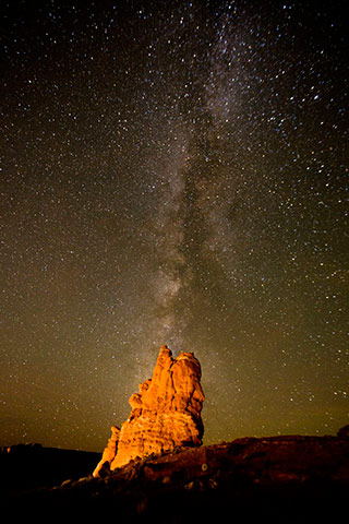 Image of the Milky Way behind a lit rock formation by Andy Long.
