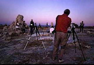 Participants of a photo workshop are set up on the rocks to make colorful sunrise images by Noella Ballenger.