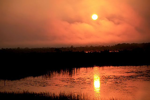 Vibrant orange sunset reflected on lake by Willis T. Bird.