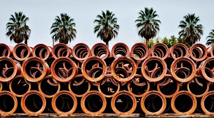 Photo of clay pipes and palm trees at the Gladding, McBean Terra Cotta Factory by Robert Hitchman