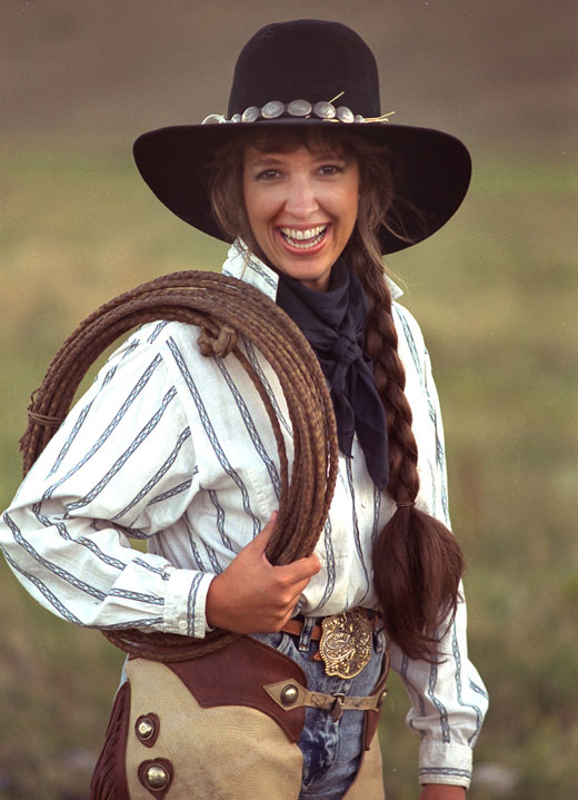 Portrait photography: cowgirl with hat, chaps and rope showing a 'real smile' by Michael Fulks.